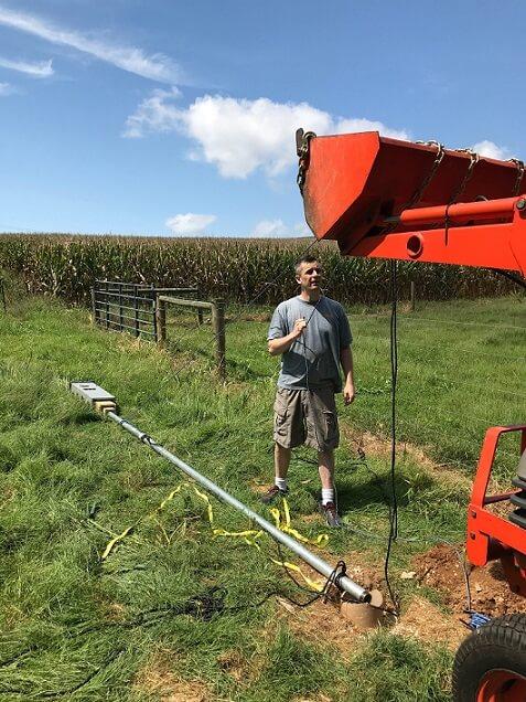 Josh standing near the bat box and pole on the ground, preparing rigging
