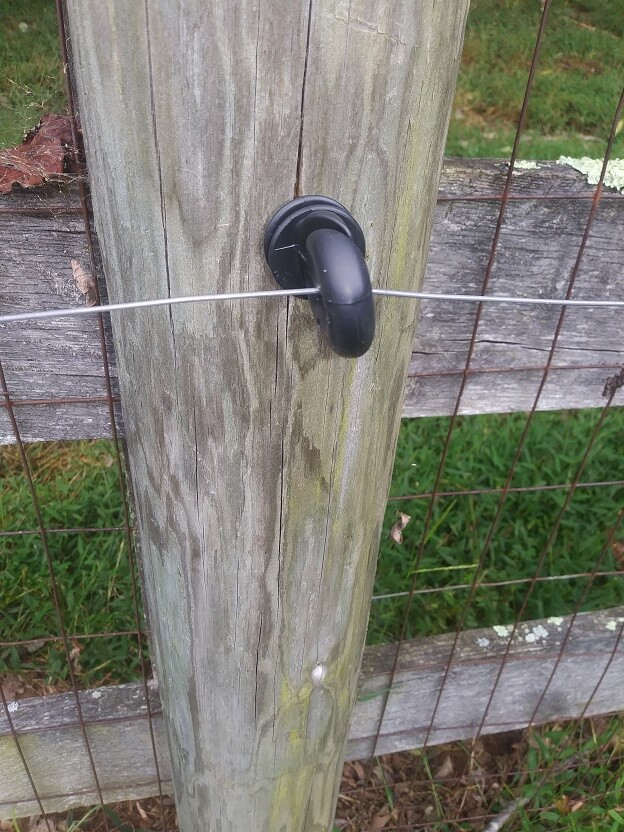 heavy duty black screw-in insulator mounted on a wood post with hot wire.  This is an easy way to fix electric fence problems.